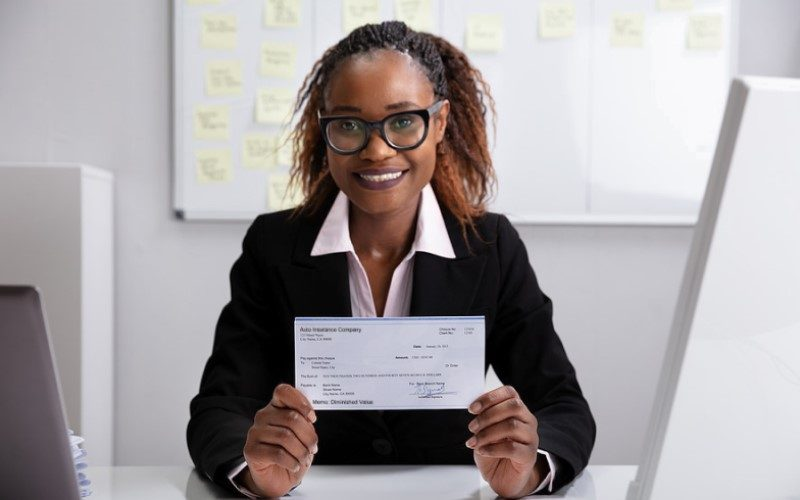 Woman holding a diminished value settlement check